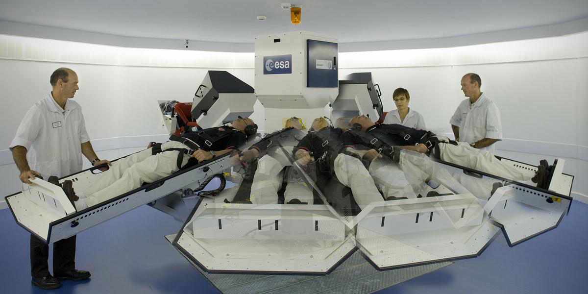 Une personne allongée dans une centrifugeuse qui tourne sous la surveillance de deux médecins